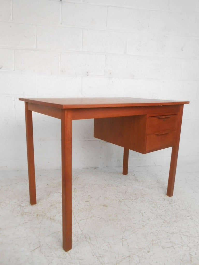 Stunning vintage modern desk features two hefty drawers with unusual sculpted pulls. Sleek compact design offers plenty of work space on the top and ample room for storage within its drawers. Quality craftsmanship with a finished back, long sturdy