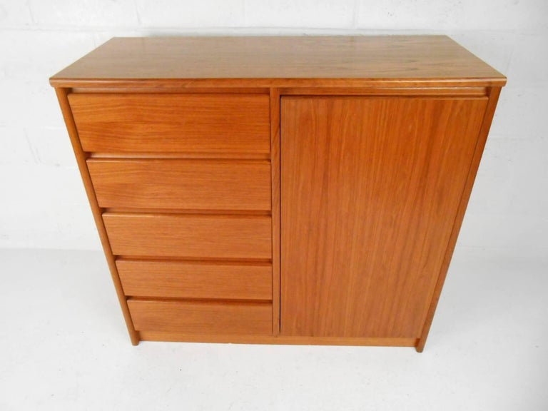 This gorgeous vintage modern armoire features plenty of room for storage within its five drawers and hidden compartment with shelving. This unique case piece displays quality craftsmanship with beautiful teak wood grain throughout. This fabulous