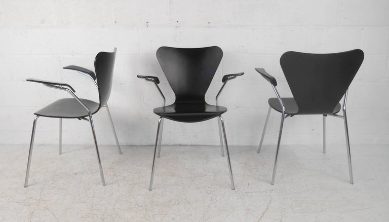 This beautiful vintage modern set of three chairs feature unique winged back rests, high arm rests, and bent rod chrome frames. Sleek design has bent black wood seating with the perfect contours ensuring maximum comfort. Unusual angled arm rests and