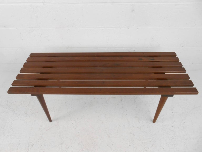 This beautiful vintage modern slat bench is made of solid walnut and features tapered legs. This unique midcentury bench makes the perfect addition to any modern interior. Please confirm item location (NY or NJ).