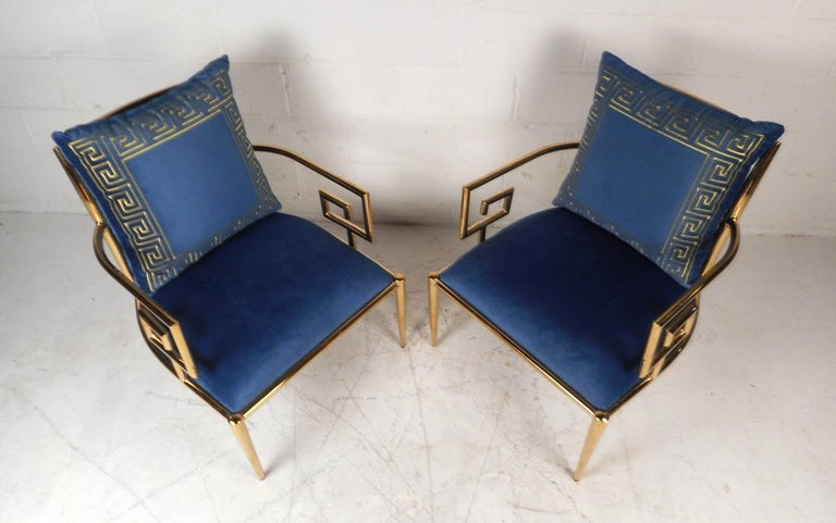 This gorgeous pair of vintage modern armchairs feature a tubular brass frame with unique arm rests. This gorgeous pair offers plenty of comfort with its thick padded seating and backrest. Lovely plush royal blue upholstery, tapered legs, and a