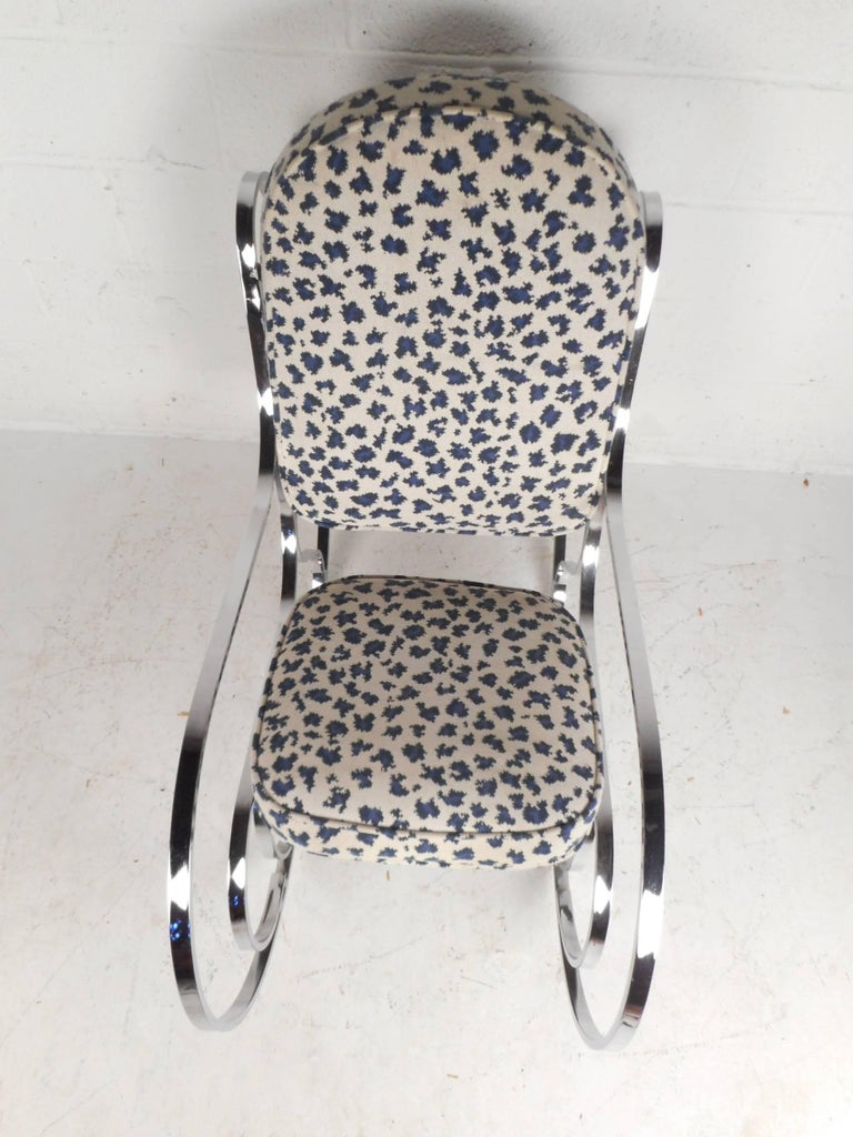 This beautiful vintage modern rocking chair features a heavy flat bar chrome frame and upholstered seating. The stylish white and blue fabric over the thick padded seating provide maximum comfort. The sculpted chrome frame makes this chair the