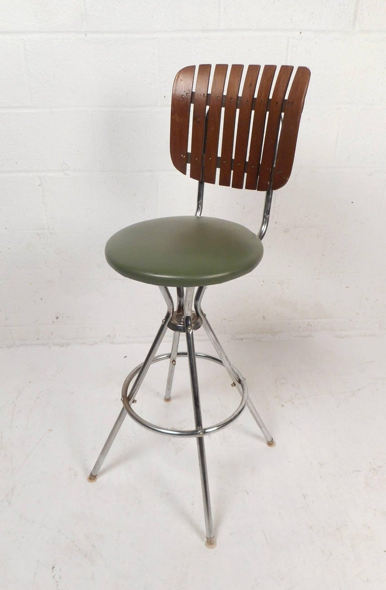 This beautiful set of four vintage modern bar stools by arthur umanoff feature uniquely shaped slatted