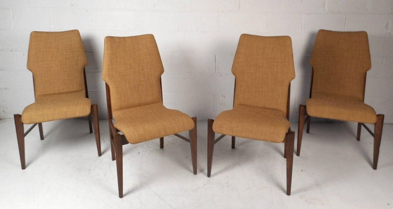 This gorgeous vintage modern set of four dining chairs feature unique walnut backs with upholstered seating. Sleek design with unique tapered legs and an unusually shaped back rest. Quality craftsmanship with elegant dark walnut wood grain and soft