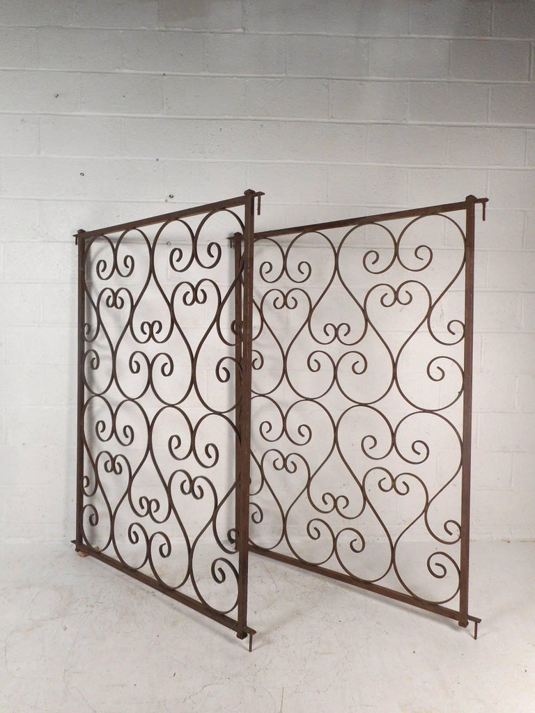 This wonderful midcentury pair of gates feature a sculpted frame with bent iron. This unique piece has heart shaped designs throughout with intricate scroll detail. The heavy and sturdy iron frame stands 64 inches tall and each gate is 46 inches