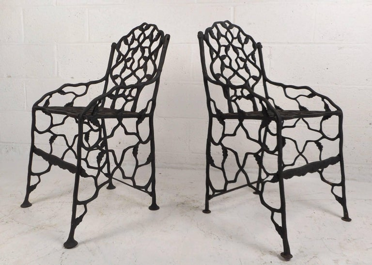 This beautiful pair of vintage cast iron garden chairs have a petite frame with bent iron and leaf detail throughout. Unusual design with a heavy iron frame, angled legs, and sculpted detail. This wonderful and rare pair of chairs make the perfect