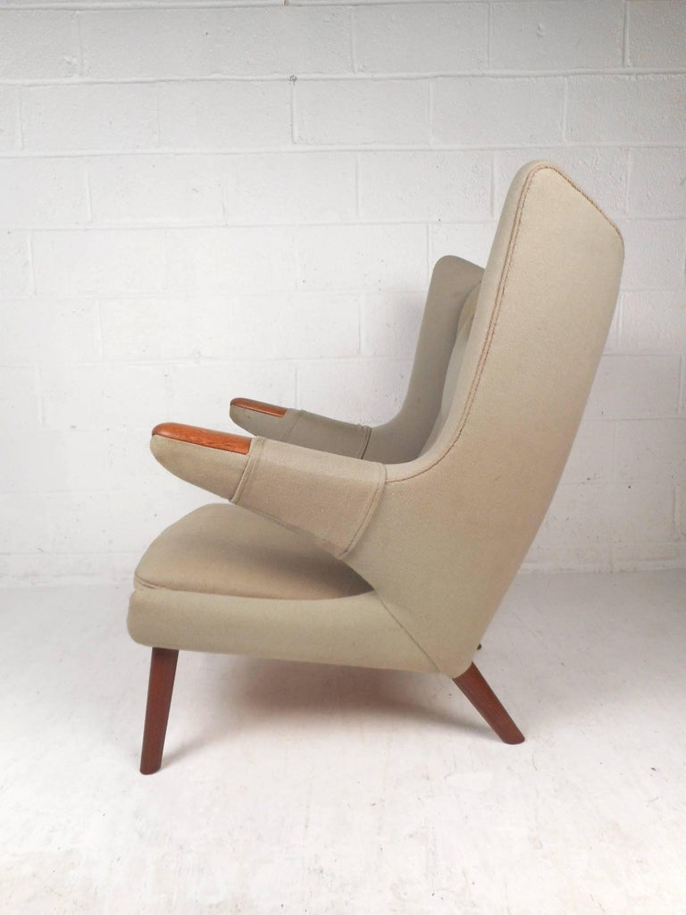 This beautiful vintage modern papa bear chair features a unique winged backrest and soft tufted upholstery. Sleek design with teak tipped armrests, splayed legs and thick padded seating. The stylish angled armrests and high backrest ensure optimal