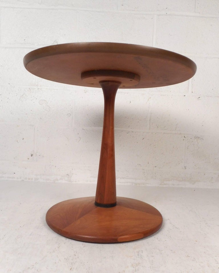 This beautiful vintage modern end table features a round top with a tulip shaped frame. Sleek design with unique wood grain on top running in different directions. This stunning side table makes the perfect eye catching addition to any modern