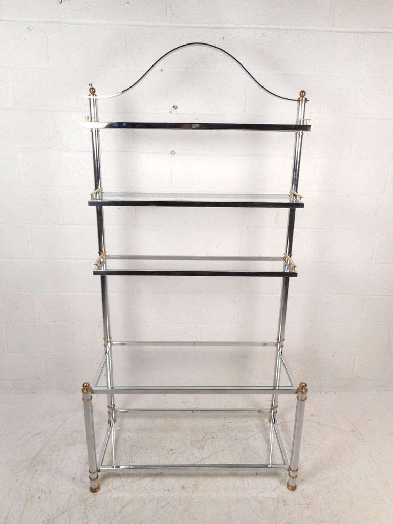 This beautiful vintage modern bakers rack features a chrome tubular frame with brass fixtures. Sleek design with five large glass shelves and a unique arch design on top adding to the allure. The top three shelves have sculpted brass fixtures on