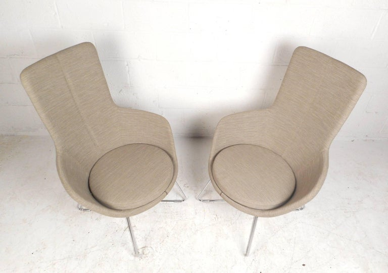 This gorgeous pair of contemporary modern lounge chairs feature unique metal rod bases with hairpin style feet. Unique design with bucket seats, a sculpted high backrest, and a thick padded cushion to sit on. This comfortable pair is covered in