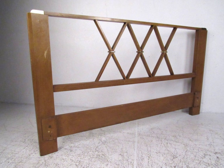Queen-size headboard in mahogany with brass corsets and accents by Paul Frankl for Johnson Furniture, circa 1940s. Please confirm item location (NY or NJ) with dealer.