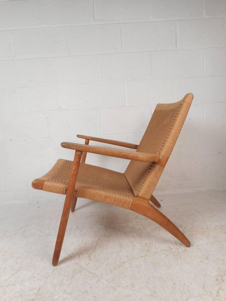 This beautiful Danish modern lounge chair features a solid oak frame with angled back legs and sculpted arm rests. Sleek design with a soft rush seat and back rest adding to the midcentury appeal. Sturdy construction with beautiful light colored