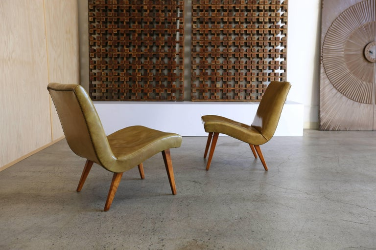 Early pair of lounge chairs by Jens Risom for Knoll. Patina to the original leather and birchwood.