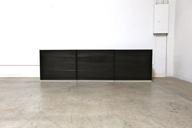 Custom ordered 12 drawer dresser by Edward Wormley for Dunbar. This piece is comprised of three separate four-drawer chest. Recently ebonized and retaining the original white leather wrapped bases.