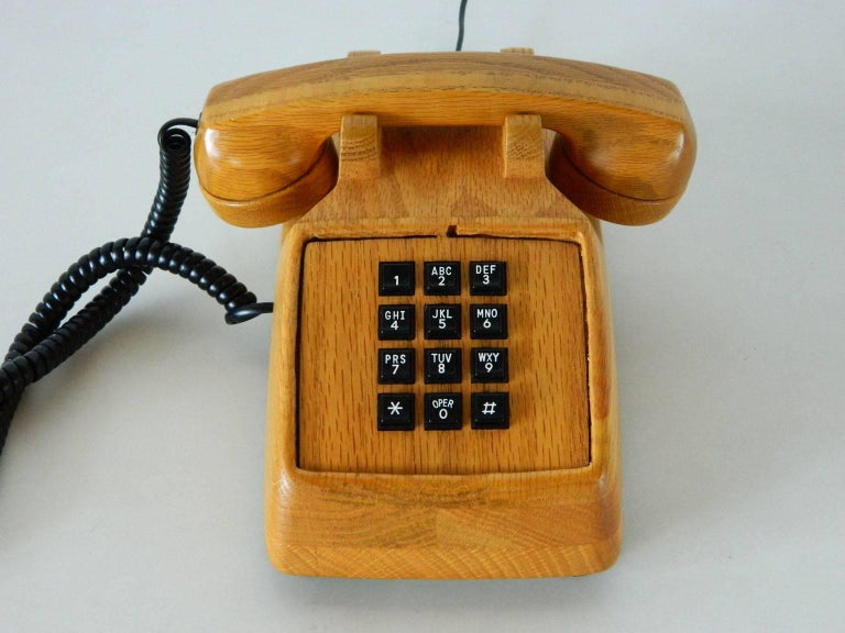 Vintage touch-tone telephone with warm wood harkens back to a time when one had to sit while talking on the phone. Manufactured in 1987, this telephone requires a landline and phone jack.