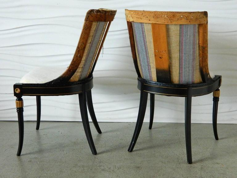 This pair of Regency-style chairs have been recently restored with black-painted finish and gold-painted details. Chairs have been stripped back and are ready for reupholstery.