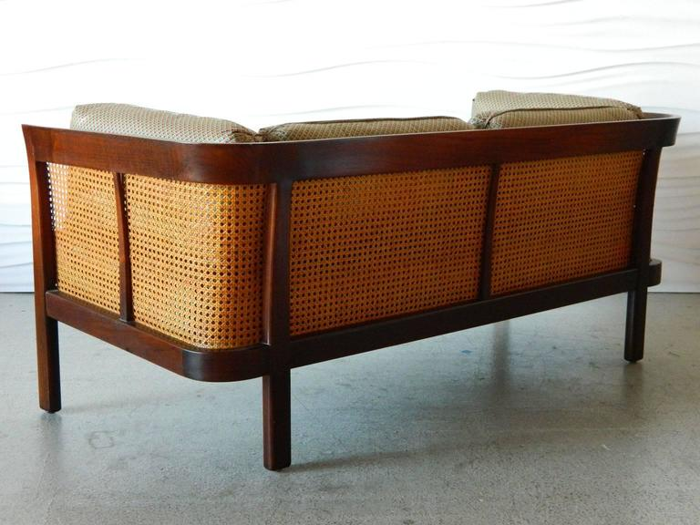 This handsome caned settee by Erwin-Lambeth features a curved walnut frame and original caning. 