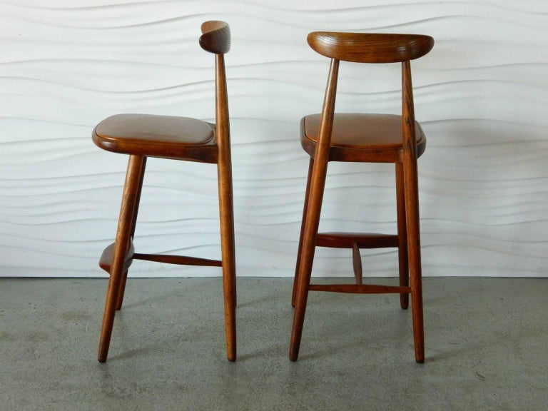 Designed by Danish architect Vilhelm Wohlert in the 1950s, this handsome pair of oak stools have teak footrests and leather-covered seats.