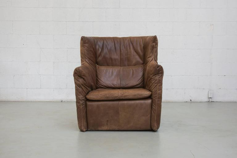 Beautiful single leather lounge chair with beautiful dark brown natural patina. Includes matching back cushion. Minor scratching and markings typical of age and use.