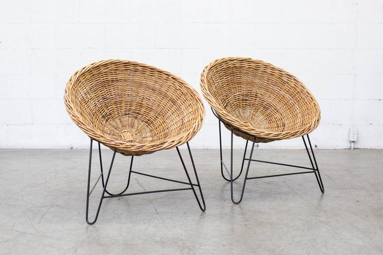 Light woven rattan basket chairs with black enameled metal frame. In original condition with visible signs of wear. Rattan and frame colors vary from chair to chair and may differ from the ones photographed Price per item.