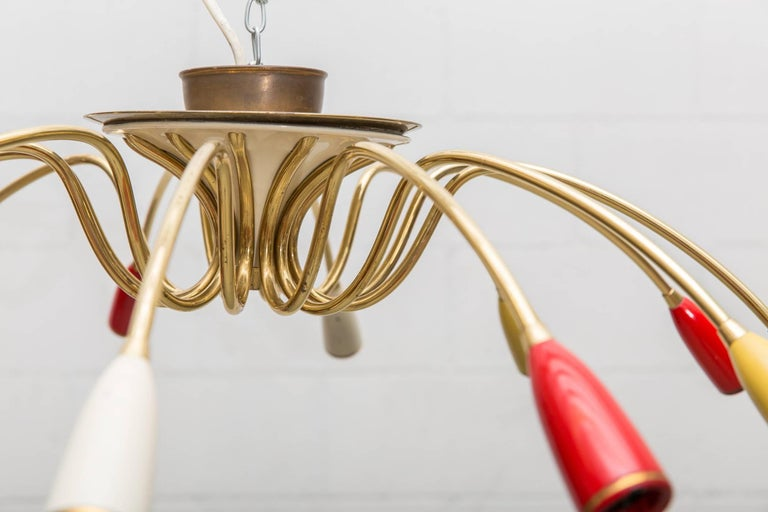 Delicate twelve-armed enameled metal and brass flush mount chandelier. Pimento, mustard and cream colored socket casings. Original condition with visible age.
