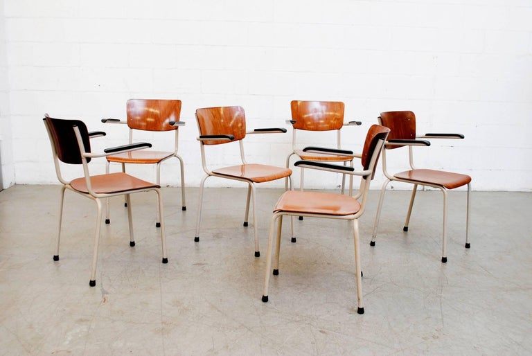 Stacking Industrial school chairs with bakelite arm rests, bone enameled metal frames and teak toned plywood seats and backs. Original condition. Frames in original condition with visible wear.