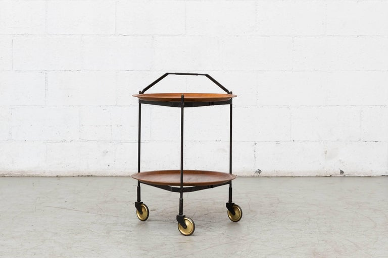 Midcentury rolling cart with two removable teak trays on collapsible black enameled metal frame and leather wrapped handle. Original brass wheels. Leather wrapped handle has been stained black, otherwise original condition.