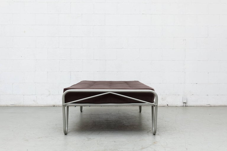 New seal grey tufted velvet mattress on an Institutional grey enameled metal single bed frame by A.R. Cordemeyer and manufactured by Kupers in Almelo, 1950s. The frame is in original condition with visible wear to the enamel. Can be disassembled for