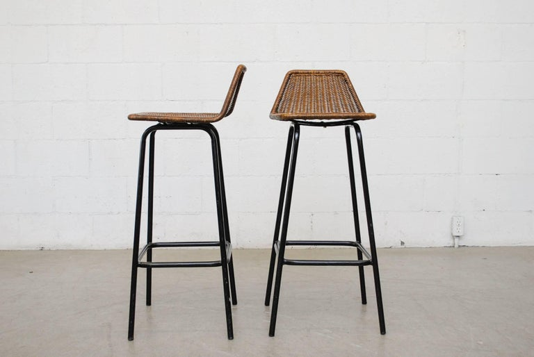 Pair of Dirk van Sliedregt tall angle backed rattan bar seat with black enameled tubular frame. Dark patina to seating, in original condition with visible signs of wear, minimal wicker and enamel loss. Set price.