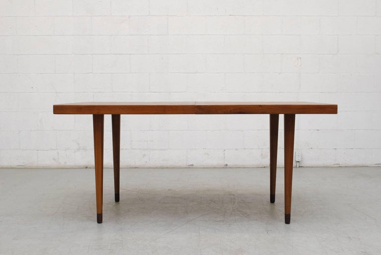 Streamline Danish teak dining table with solid teak tapered legs and hidden extension leaf. In good original condition. Originally low table with removable extensions added. Gorgeous table.