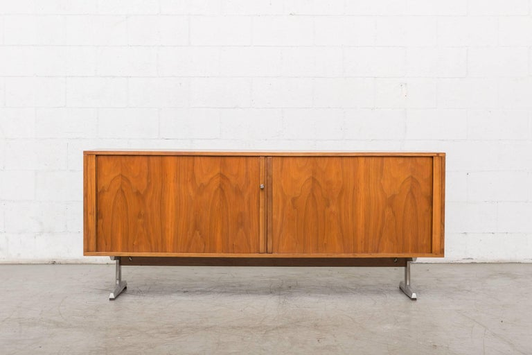 Midcentury teak credenza. Beautiful sliding tambour doors with three sections of interior storage with adjustable shelves. Enameled metal base with chrome T-shaped legs. Good original condition. Key lock.