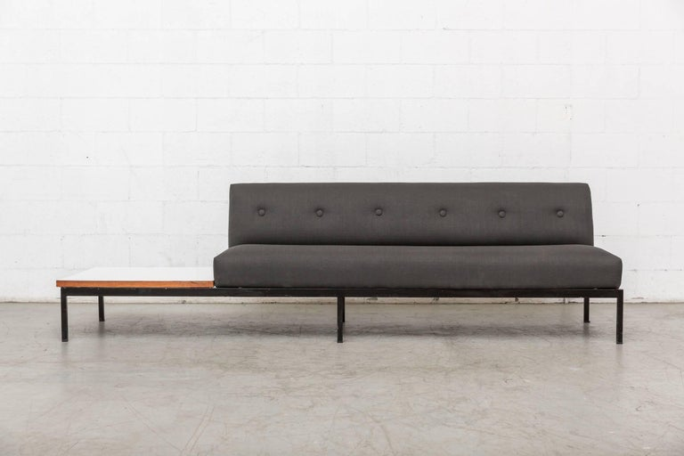 Gorgeous midcentury three-seat Kho Liang Ie sofa for artifort with white formica side table with teak border. Newly upholstered in grey fabric with black enameled metal frame. Table and seating can be oriented to either left or right side of sofa.