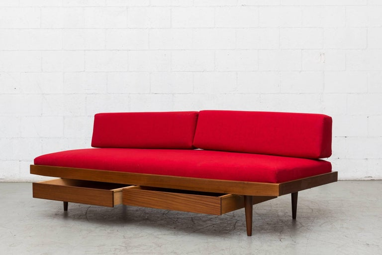 Charlotte Perriand inspired midcentury daybed with tapered legs, double storage drawers and new lipstick red upholstered mattress and bolsters. Has pegboard support. Good original condition, lightly refinished. Others available in different color
