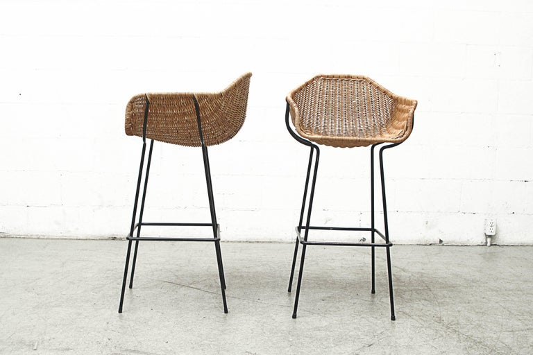 Gorgeous pair of original bar stools with woven rattan bucket seats and black enameled metal frames. Original condition with visible signs of wear consistent with its age and usage. Set price.