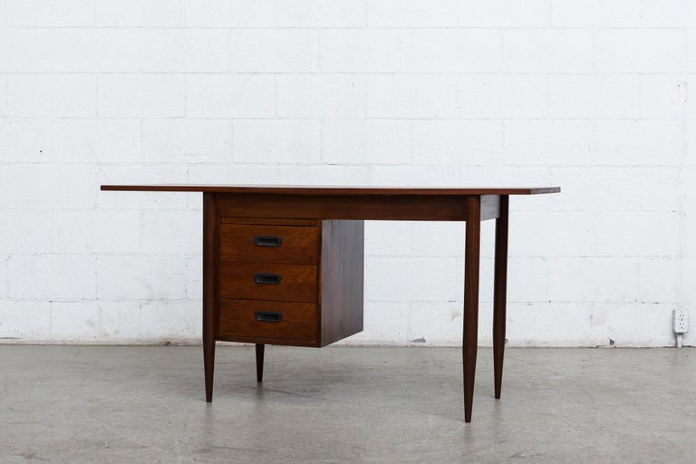 Arne Vodder style little teak desk with top extension. The extension flips up and slides to the right to make a larger writing surface. Lightly refinished teak with round teak legs, three side stacked drawers and acrylic hand pulls. In good original