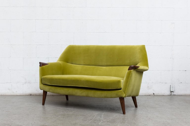 Midcentury 1950s loveseat newly upholstered in kiwi velvet with inset wood armrests and tapered wood legs. Good original condition.