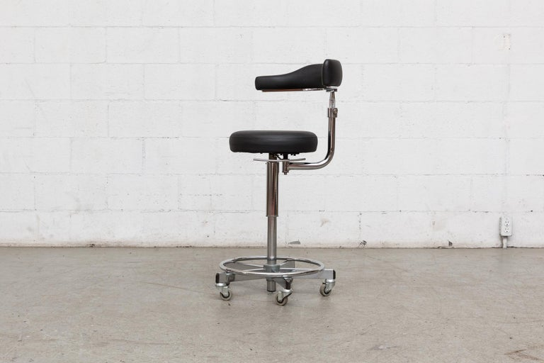Rolling German dentist chair with asymetric seat back, black leather upholstery and chrome frame with adjustable height. Rubber bumper details on footrest.