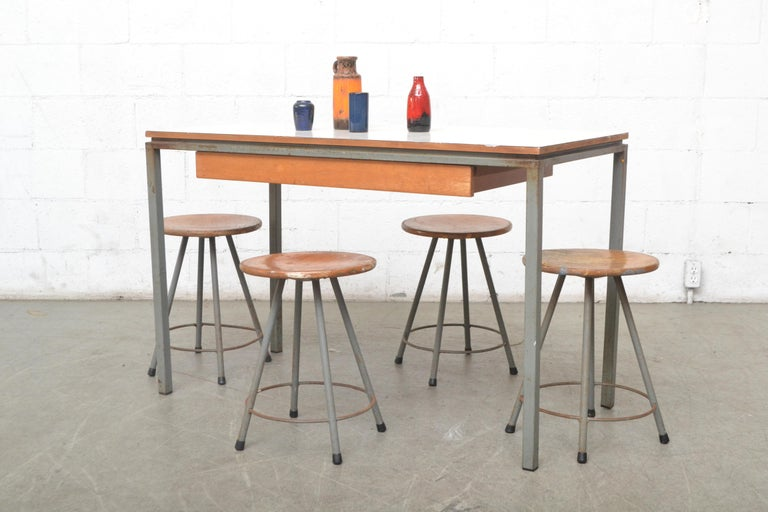 Early edition Marko industrial task or dining table with four matching stools. Both have grey enameled metal tubular frames, lightly refinished natural wood. Table has a white formica top and long storage drawer. Stools measure - 13.25 x 13.25 x