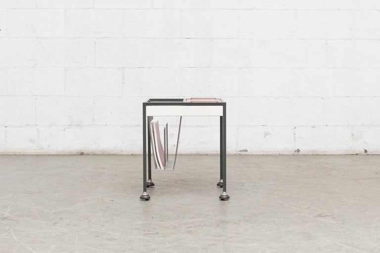 Midcentury rolling cart with wire-framed magazine rack, small teak covered storage bin on top with removable chrome retractable handles. Grey and white enameled metal frame. Original condition.