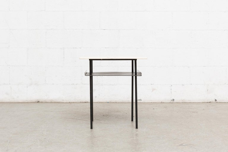 Smaller version of this side table in painted off-white plywood top with enameled black metal frame and perforated sheet metal lower shelf with bent edges. In original condition with visible wear to the top and frame.