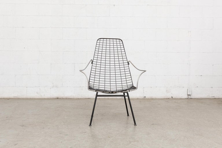 Black enameled metal and chrome wire framed armchair. Bent chrome tubular arm rests with woven black enameled metal body and thin black enameled metal legs. Good original condition.