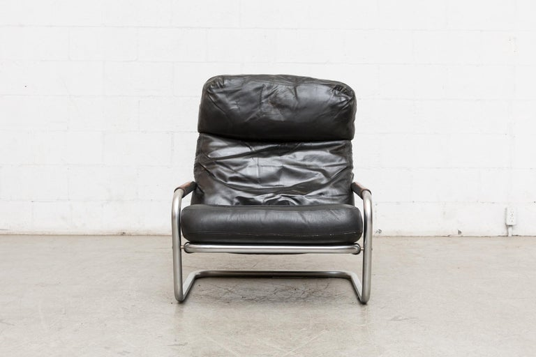 "Jan des Bouvries masculine black leather lounge chair with fat chrome tubular frame. Model number S601 also known as the ""Oberman"". Handsome silhouette, thick leather wrapped arm rests with well worn black leather cushions. In very original"