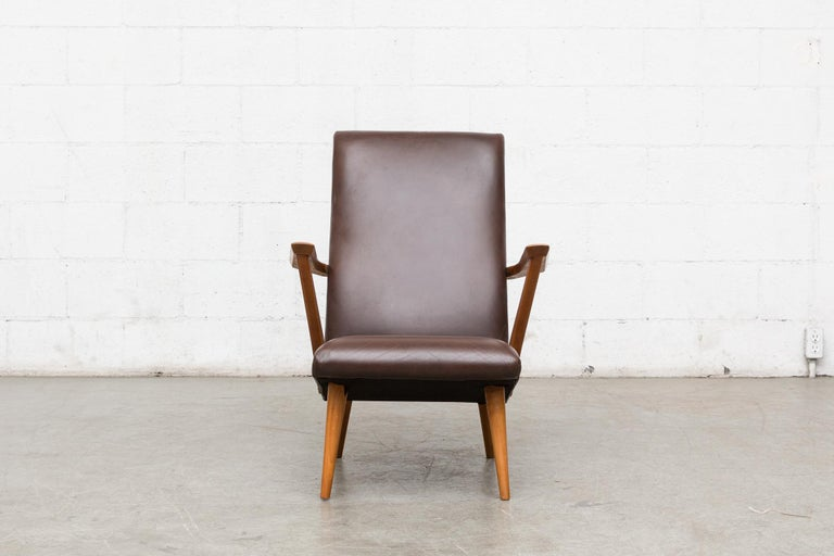 Mid-century lounge chair with original brown leather upholstery. Lightly refinished angular teak arms and legs. Good original condition.