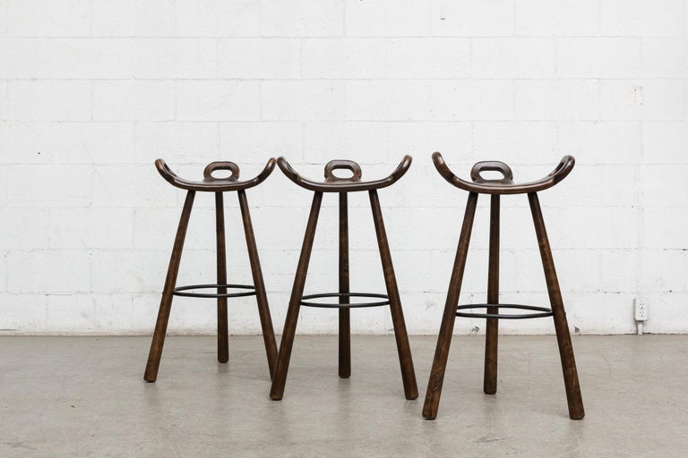 Set of 3 lightly refinished Spanish brutalist bar stools by Sergio Rodriguez. Dark oak frames with black enameled metal circular foot rests. Wear consistent with age and usage. Set price.