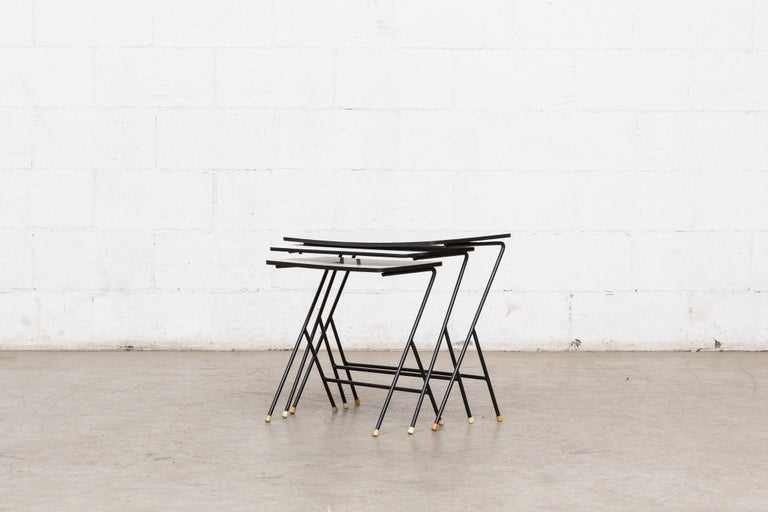Set of 3 zig-zag mategot inspired nesting tables with grey and white Formica tops, black enameled metal wire frames and original rubber tipped feed. Visible cracking and staining to top table. Visible wear. Set price.