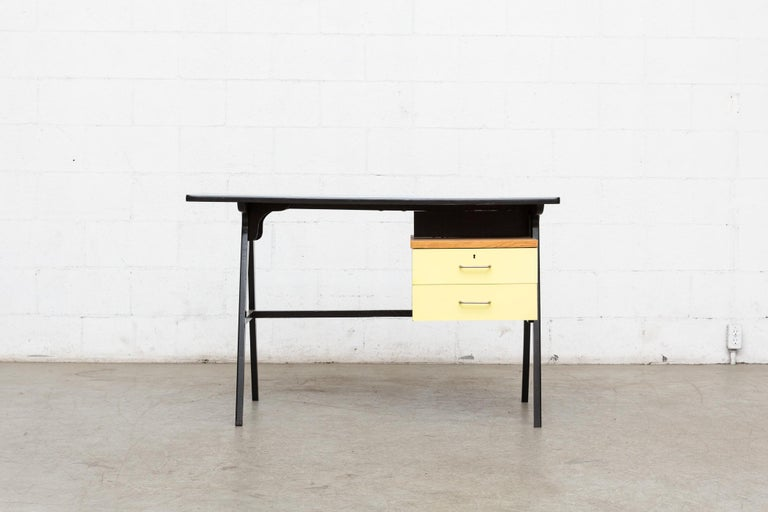Midcentury wood writing desk with original sky blue formica top and yellow formica faced drawers with brushed chrome hand pulls. Wood frame is painted black. Original condition with visible wear. and Patina.