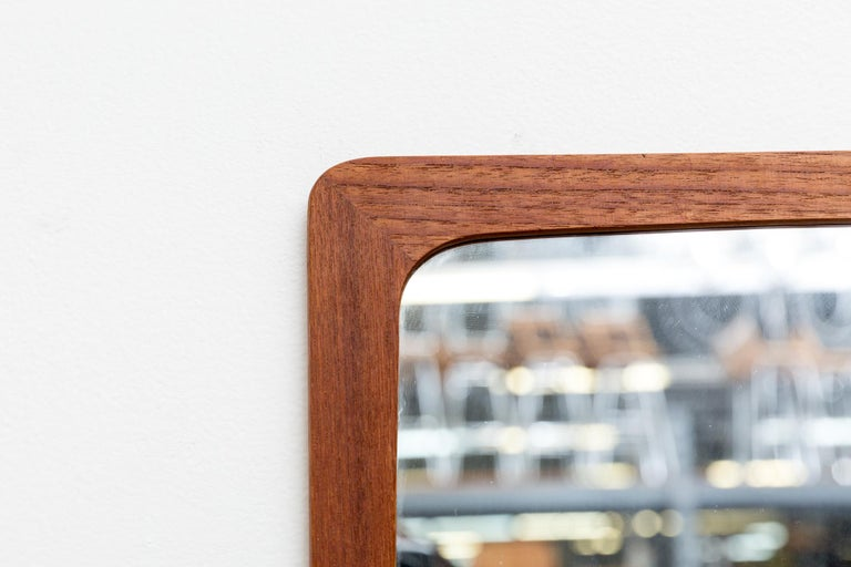 Handsome Danish wall mount teak mirror with small cubby shelf. Good original condition.