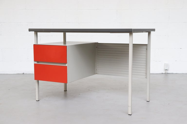 Midcentury Industrial metal desk by A. R. Cordemeyer for Gispen. Light grey enameled metal desk with corrugated metal privacy screen, red enameled metal drawers and grey linoleum top. Visible wear, some scratching and metal loss. Wear is consistent