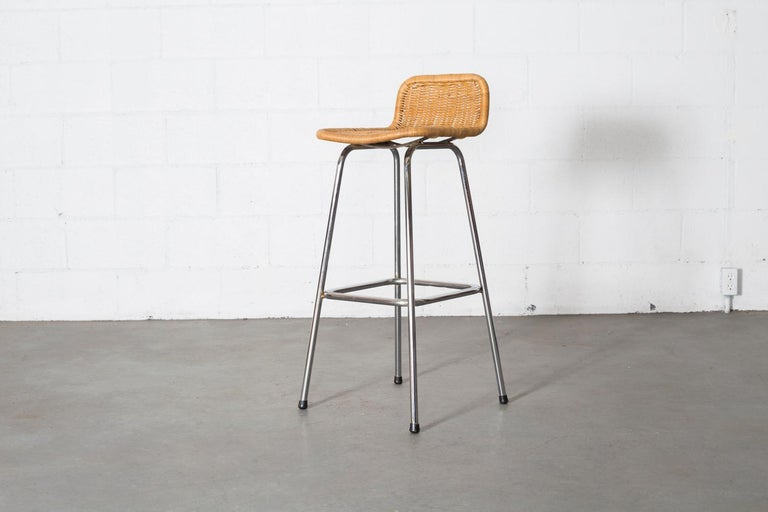 Charlotte Perriand style bar stools with low, rounded rattan seat and back with chrome tubular frame. In original condition.