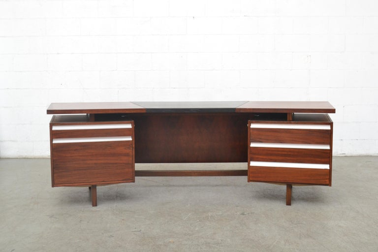 Impressive midcentury executive desk by Fristho. Lightly refinished rosewood with original black skai top. Visible wear and some scratches on the vinyl top. Right side has three sliding drawers and a filing cabinet and top drawer with sliding wood